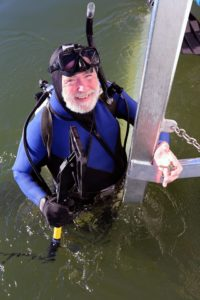 Dr. E. Lee Spence with underwater metal detector made by Secon. He is also holding one of the more than 60 small crosses and crucifixes his team found on a yet to be identified shipwreck that he discovered in about 15 feet of water over three nautical off the coast of South Carolina. Spence has the exclusive rights and ownership to the wreck through a court order.